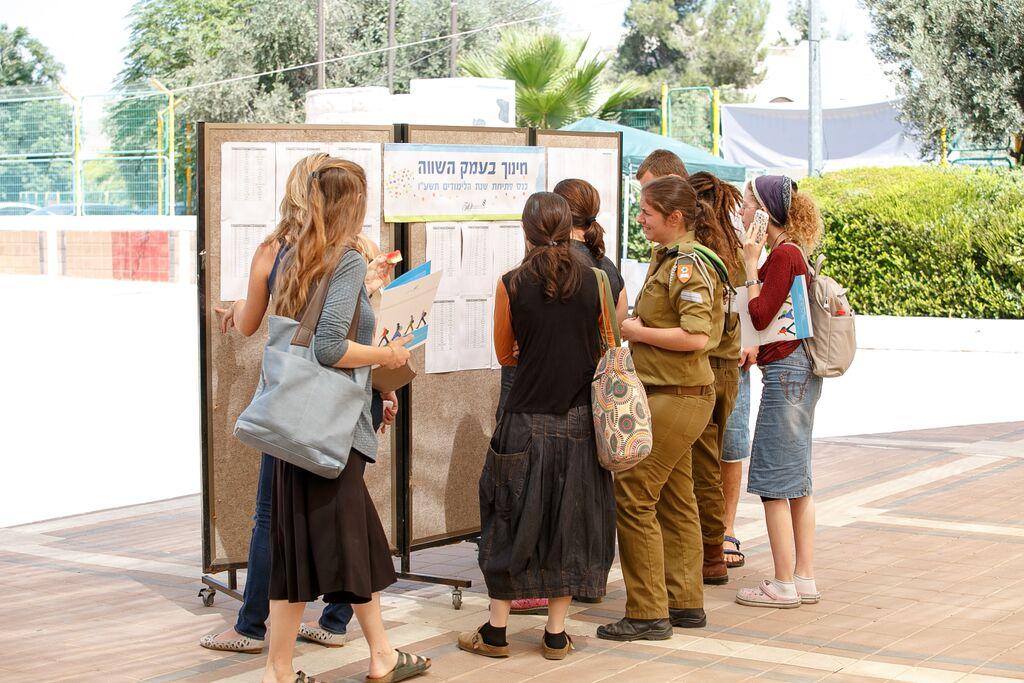 בנות עומדות ליד לוח מודעות ביום עיון