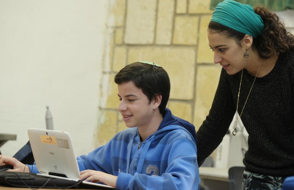 מורה עוזרת לתלמיד מול המחשב