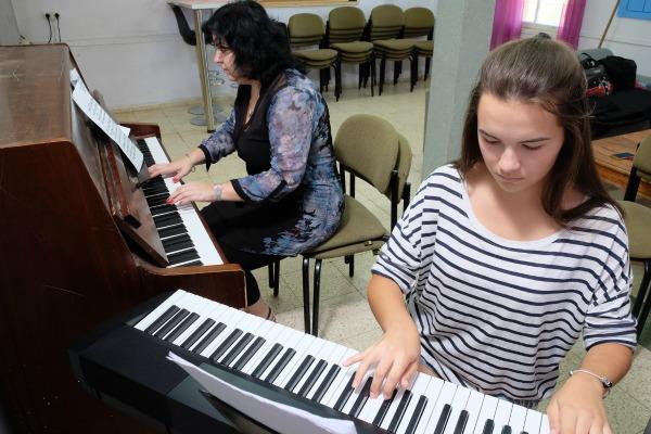 תלמידה-ומורה-בשיעור-נגינה-על-פסנתר