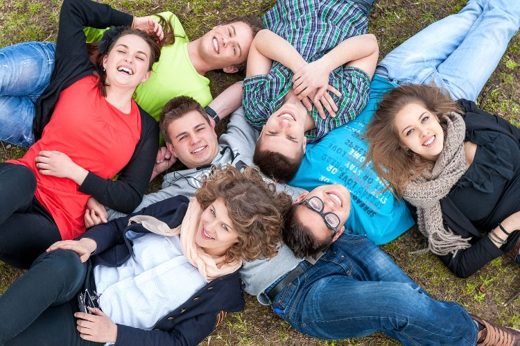 Happy teenagers lying on lawn shot from above